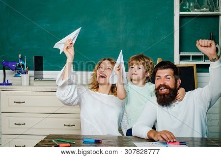 Pupil With Paper Airplane Playing With Parents. Young Couple Helping His Son To Make Homework. Paren