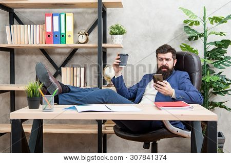 Mobile call. Start day with coffee. Coffee relaxing break. Boss enjoying energy drink. Man bearded businessman hold cup and smartphone. Coffee is pledge of successful negotiations. Caffeine addicted. poster