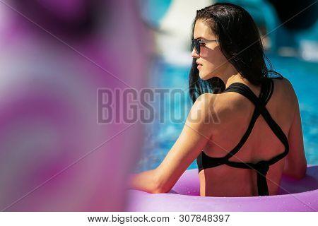 Beautiful Woman With Perfect Figure In Black Swimwear In Pink Rubber Ring In The Swimming Pool. Summ