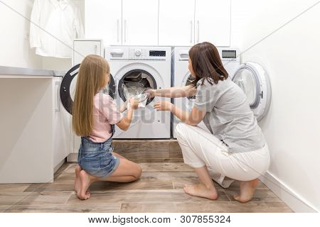 Mother And Daughter Helper In Laundry Room Near Washing Machine And Dryer Pulling Off Clean Clothes