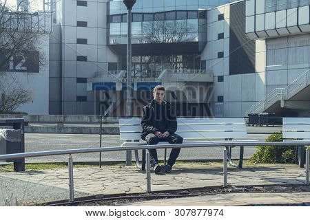 Portrait Of A Sad Young Man Sitting On A Bench