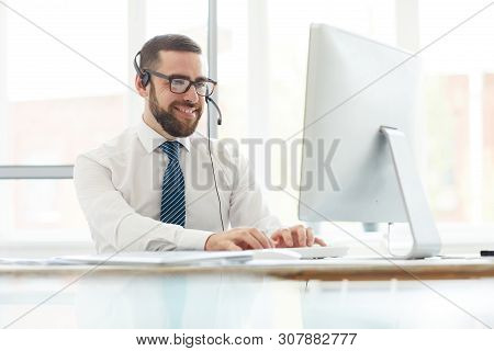 Positive Handsome Young Switchboard Operator In Headset Sitting At Table And Typing On Computer Keyb