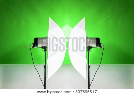 Photography Studio Flash Strobe For Light And Picture Taking On Green Color. Tools For Professional