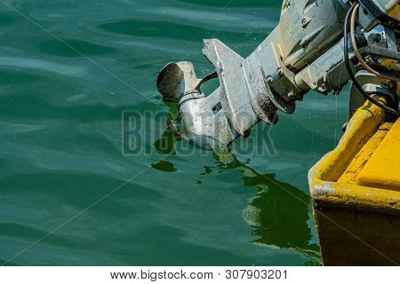 Outboard Motor On Yellow Boat In Greenish Water On Sunny Day.