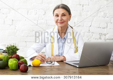 Indoor Shot Of Positive Smiling Caucasian Female Nutritionist In Her Sixties Working Online, Sitting