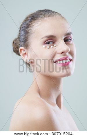 Smiling Young Woman With Pink Eye Shadows And Pearls On Lower Lid