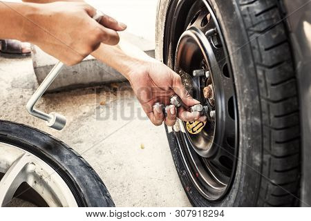 Hands Of Mechanic Pick Up The Nut Of Car Wheel.change A Flat Car Tire At Car Park With Tire Maintena