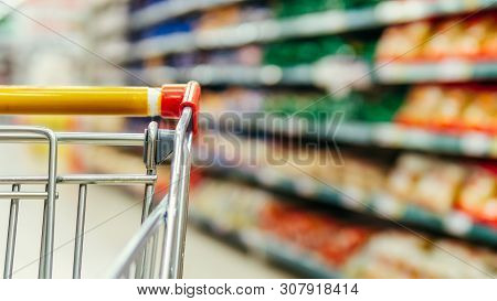 Shopping Cart In Supermarket. Part Of Shopping Trolley In Supermarket Aisle. Blurred Shelves In Groc