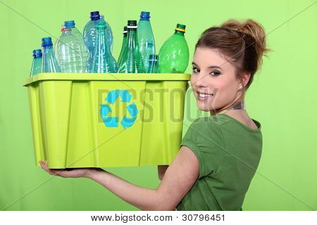 Woman recycling crate of plastic bottles