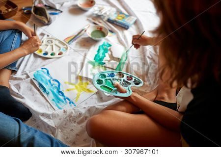 Young people painting with temperas