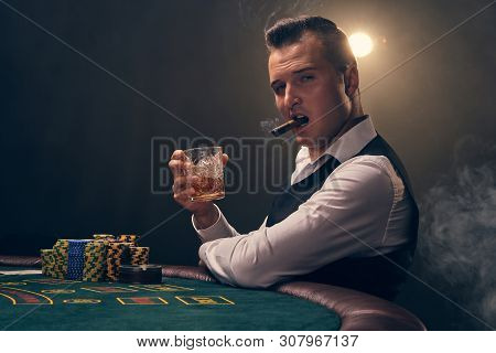 Wealthy man is smoking a cigar and playing poker with an excitement at a casino on black background. poster