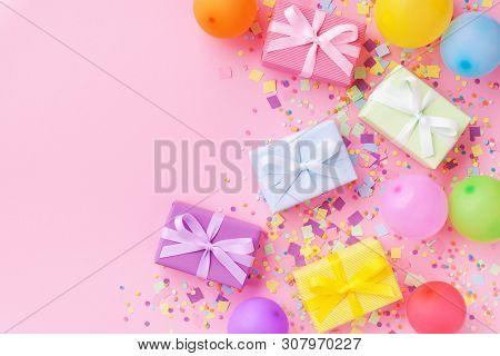 Gift Or Present Boxes, Colorful Balloons And Confetti On Pink Pastel Table Top View. Birthday Party