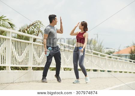 Excited joggers giving each other high five after training outdoors poster