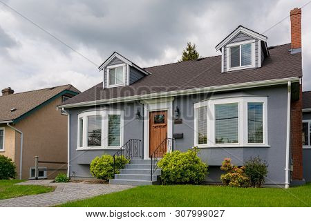 Family House With Green Lawn And Decorative Bushes In Front.  Average Residential House On Cloudy Da