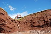 A refurbished red barn atop the red clay cape in PEI Canada poster
