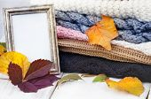Stack of knitwear with frame empty copy space. Autumn season template. poster