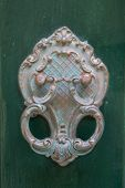 An old style decorative bronze door handle on a wooden green door, the distinctive feature and symbol of Malta in Mdina. poster