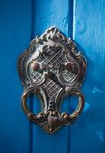 An old style decorative bronze door handle on a wooden azure door, the distinctive feature and symbol of Malta in Mdina. poster