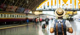 Young Man Traveler With Backpack Waiting For Train, Asian Backpacker With Hat Standing On Railway Pl