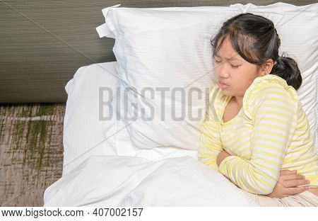 Child Is Lying On The Bed And Holding Her Belly. Medication And Health Concept. Stomach Ache. Suffer