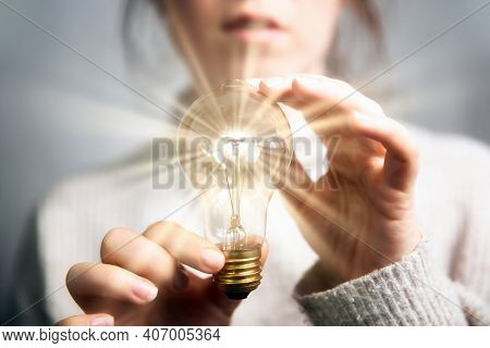 Female Hand Holding A Shining Light Bulb, Great Idea, Innovation And Inspiration, Business Concept B