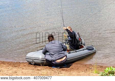 Fishermen Are Preparing To Sail In An Inflatable Boat With An Outboard Motor To Set Off On A Fishing