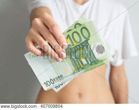 In The Outstretched Female Hand, 100 Euro Bills. The Woman Holds Out The Money. The Concept Of Wealt