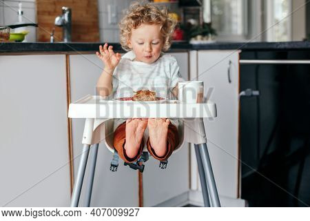 Cute Happy Caucasian Curly Kid Boy Sitting In High Chair Eating Homemade Apple Pie And Drinking Juic