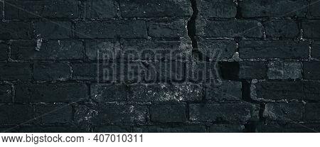 Cracked Blue Brick Wall With Big Crack Structure. Dark Damaged Brickwork Surface Texture. Destroyed