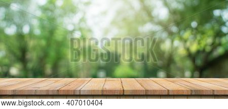 Empty Wood Table And Defocused Bokeh And Blur Background Of Garden Trees With Sunlight. Product Disp