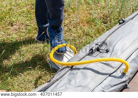 Inflatable Boat Pumping Process, Close-up. A Fisherman Pumps An Inflatable Boat With A Foot Pump.