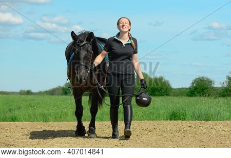 Smiling Caucasian Woman, 40 Years Old, Is Holding The Reins Of Her Saddled Horse And Walking On The