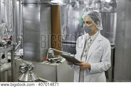 Waist Up Portrait Of Female Worker Wearing Mask And Holding Digital Tablet During Quality Control In