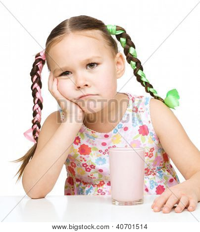 Menina triste não quer beber leite, isolado sobre o branco