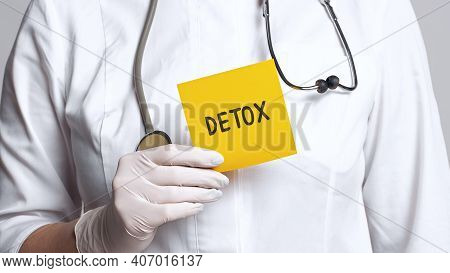 Cropped View Of Doctor In A White Coat And Sterile Gloves Holding A Note With Word - Detox. Medical