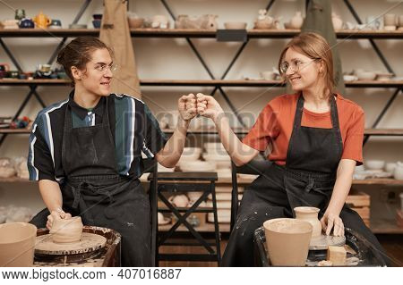 Front View Portrait Of Two Young Artisans Bumping Fists While Making Ceramics In Pottery Workshop Wi