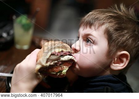 Portrait Of Boy Has Burger In Dark Restaurant