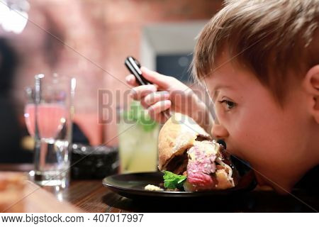 Child Has Burger In Dark Restaurant