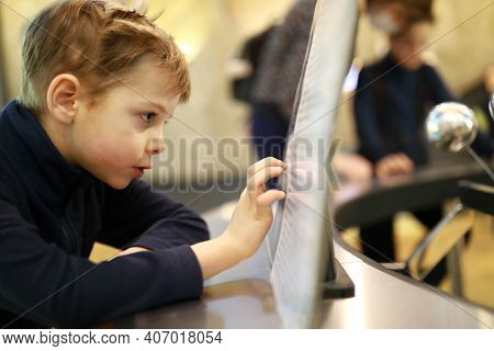 Curiosity Child Using Touch Screen In Museum