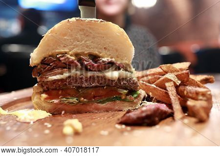 Half Burger With Fries On Wooden Board In Pub