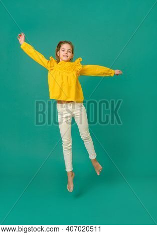 White Teenage Girl 10 Years Old In A Yellow Blouse And White Pants Jumps On A Green Background