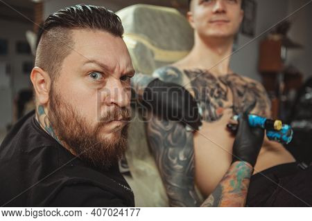 Bearded Professional Tattoo Artist Making Angry Face To The Camera, While Working With His Male Clie