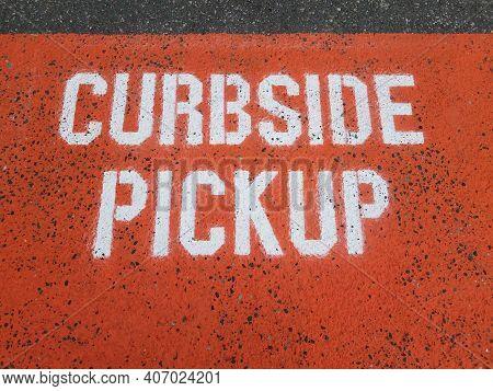 Orange Curbside Pickup Sign On Asphalt Or Ground