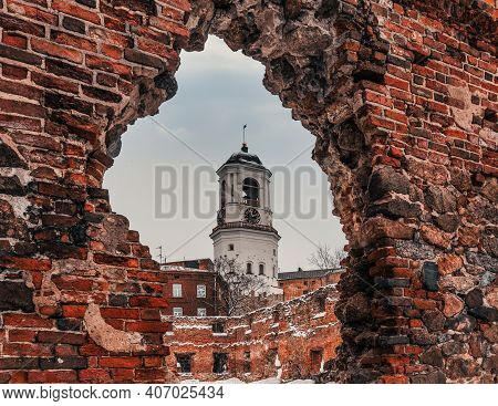 Vyborg Clock Tower. Belfry Of The Vyborg Cathedral. View Of The Clock Tower Through The Ruins Of The