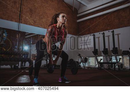 Full Length Shot Of A Beautiful Muscular Female Athlete Doing Kettlebell Swings, Exercising At The G