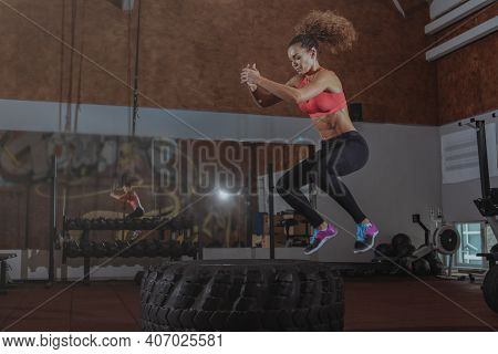 Beautiful Fit Sportswoman Exercising At Box Gym, Jumping High On A Huge Tire. Energetic Female  Athl