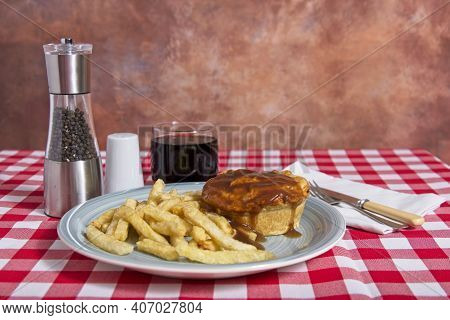 Beef Pie With Gravy And Chips On Pale Blue Plate On Red And White Check Tablecloth With Lass Of Cold
