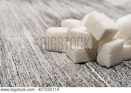 Sugar Cubes Lie On A Wooden Background Of Gray Color. Sugar. Refined Cane Sugar