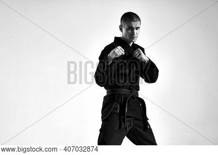 Confident Male In Kimono Fighter Posing In Karate Stance On Studio Background With Copy Space, Black