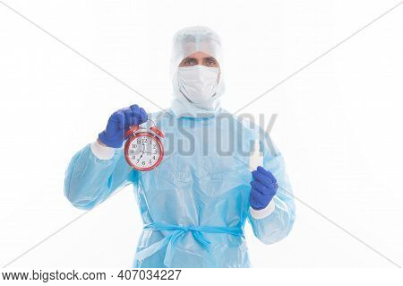 Physician In Personal Protective Equipment Hold Alarm Clock And Prescribed Covid-19 Medicine For Reg